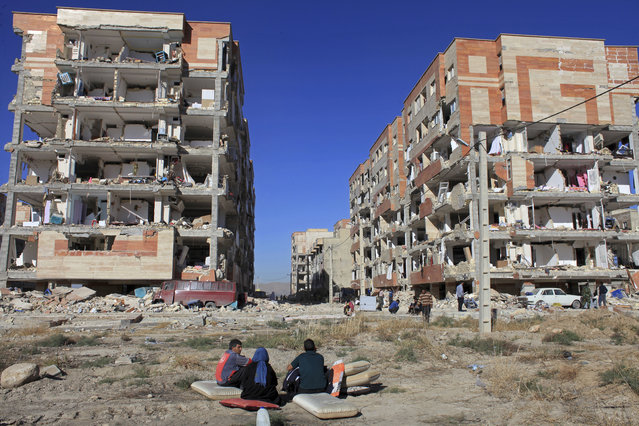 Survivors sit in front of buildings damaged by an earthquake, in Sarpol-e-Zahab, western Iran, Monday, November 13, 2017. A powerful 7.3 magnitude earthquake that struck the Iraq-Iran border region killed more than three hundred people in both countries, sent people fleeing their homes into the night and was felt as far west as the Mediterranean coast, authorities reported on Monday. (Photo by Omid Salehi/AP Photo)