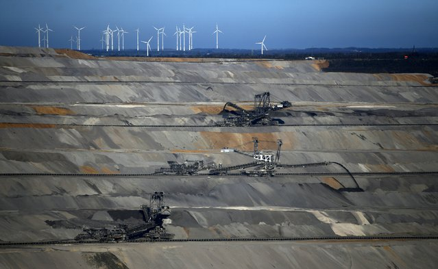 """A picture taken on January 16, 2020 near Buir shows excavators at the Hambach open-pit lignite (brown coal) mine operated by German energy producer RWE in Niederzier and Elsdorf, western Germany. The mine is in the focus of environmentalists for years, as power generation using lignite has a negative impact on the climate change, and also because RWE plans to clear the ancient """"Hambacher Forst"""" forest in order to enlarge its mine. (Photo by Ina Fassbender/AFP Photo)"""