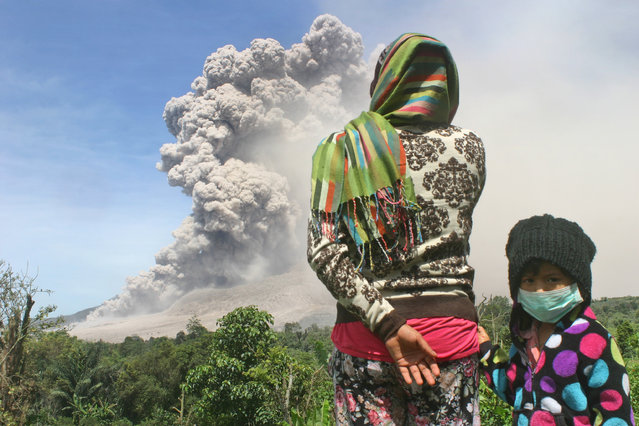 """Villagers watch as Mount Sinabung spews volcanic materials during an eruption in Tiga Serangkai village, North Sumatra, Indonesia, Thursday, October 9, 2014. Lying in the Pacific """"Ring of Fire"""", Indonesia has 127 active volcanoes, more than any other countries in the world. (Photo by Rio Siregar/AP Photo)"""