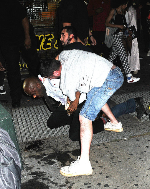 A man with broken bottle glass slashes two other men on 14th Street in Manhattan, New York on August 27, 2016. The man who is unnamed was later arrested by police following the fight as he ran down a street with the broken bottle. Pictured: Man with broken bottle glass slashes two other men. (Photo by Demis Maryannakis/Splash News and Pictures)
