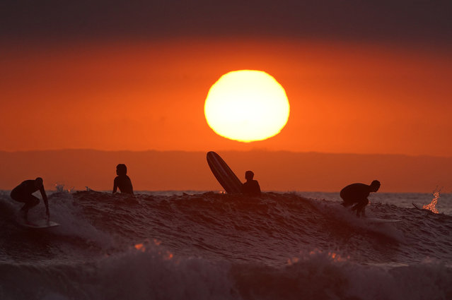 Surfers ride as the sun goes down the day before the beach is scheduled to close during the coronavirus outbreak, Thursday, April 30, 2020, in Newport Beach, Calif. California Gov. Gavin Newsom on Thursday temporarily closed Orange County's coastline after large crowds were seen there. (Photo by Mark J. Terrill/AP Photo)