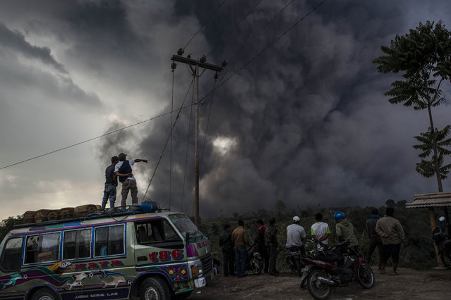 People watch as Mount Sinabung spews pyroclastic smoke at Tiga Pancur village on October 13, 2014 in Berastagi, Karo district, North Sumatra, Indonesia. (Photo by Ulet Ifansasti/Getty Images)