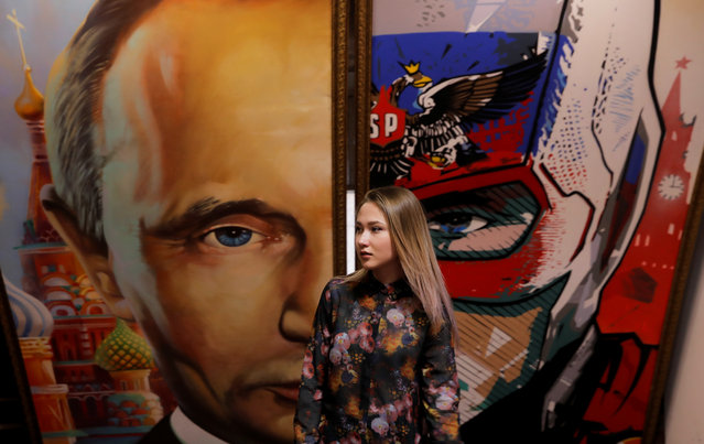 """A woman stands in front of a painting depicting Russian president Vladimir Putin at the """"SUPERPUTIN"""" exhibition at UMAM museum in Moscow, Russia on December 6, 2017. (Photo by Maxim Shemetov/Reuters)"""