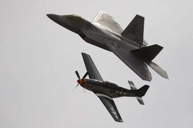 Pilot Kevin Eldridge in a P-51 Mustang and an F-22 Raptor fighter jet piloted by Major John Cummings perform a U.S. Air Force Heritage Flight at the California International Airshow in Salinas, California, September 27, 2015. (Photo by Michael Fiala/Reuters)
