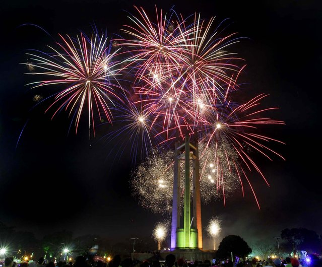 Spectators watch a fireworks display at the Quezon Memorial Circle in suburban Quezon city, north of Manila, Philippines. (Photo by Aaron Favila/Associated Press)