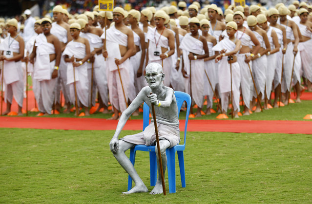 Shri Gopal, a Gandhian or follower of Gandhi's philosophy, sits dressed as India's independence leader Mahatma Gandhi, as he is joined by school children also dressed as Gandhi in an attempt to create a Guinness record, during celebrations to mark Gandhi's birth anniversary in Bangalore, India, Friday, October 2, 2015. 4605 children participated in the event to break the record of largest gathering of people dressed as Gandhi, according to organizers. (Photo by Aijaz Rahi/AP Photo)