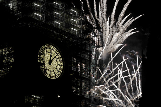"""Fireworks explode over the River Thames behind the Elizabeth Tower which contains the bell know as """"Big Ben"""", at the Houses of Parliament in London, as New Year's celebrations take place after midnight, Monday, January 1, 2018. Scaffolding stands erected around the Elizabeth Tower for repairs, with the last extensive conservation works taking place more than 30 years ago. (Photo by Matt Dunham/AP Photo)"""