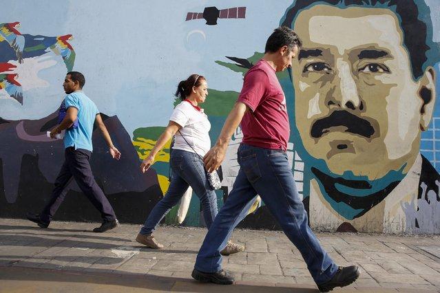 People walk past a mural depicting Venezuela's President Nicolas Maduro in Caracas August 13, 2015. (Photo by Carlos Garcia Rawlins/Reuters)