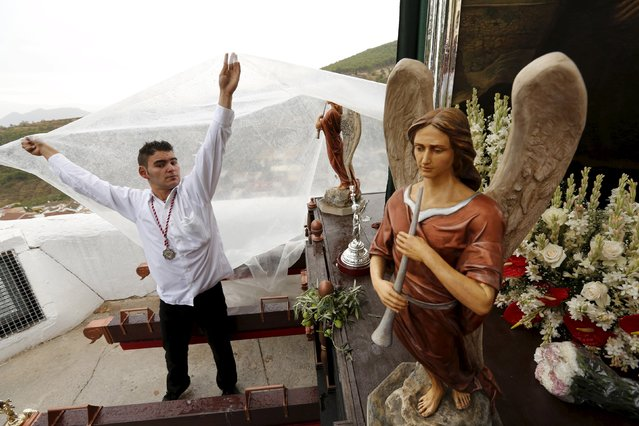 A devotee covers the Christ of Pano platform from the rain during a pilgrimage in Moclin, southern Spain, October 5, 2015. (Photo by Marcelo del Pozo/Reuters)