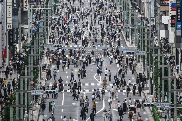 People walk on a street in Tokyo on July 24, 2020. Some 260 new cases COVID-19 coronavirus infections were recorded in the Japanese capital on July 24. (Photo by Charly Triballeau/AFP Photo)