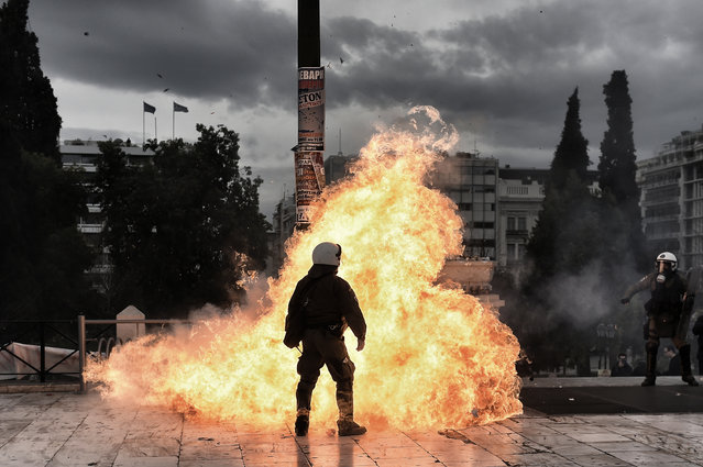 A firebomb explodes beside a riot police member during a massive protest on February 4, 2016. Thousands of people marched across Greece on February 4, 2016 as diverse classes united in a crippling general strike over a pension overhaul that has sparked a major backlash against embattled leftist Prime Minister Alexis Tsipras. (Photo by Aris Messinis/AFP Photo)