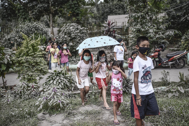 Residents wear face masks amidst heavy ashfall at an evacuation center in Camalig, Albay province, Philippines, January 24, 2018. (Photo by Ezra Acayan/NurPhoto via Getty Images)