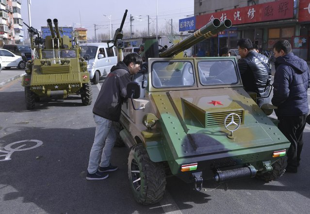 People look at home-made armoured vehicle look-alikes on a street in Shenyang, Liaoning province, November 12, 2014. A man surnamed Zhang and his friends converted two cars into these two vehicles, for his son, and will be displaying them on show at a local park. The cannons on the vehicles can fire paintballs and smoke shells, local media cited Zhang as saying. (Photo by Reuters/Stringer)