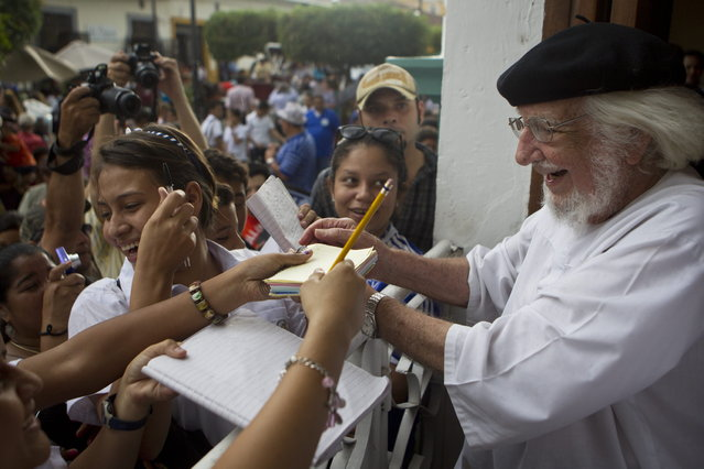 Nicaraguan poet, priest and former Minister of Culture of Nicaragua, Ernesto Cardenal, signs autographs during celebrations marking the 9th International Poetry Festival in his honor in Granada, Nicaragua, Wednesday, Feb 20, 2013. The festival is attended by more than 300 poets from some 60 countries. (Photo by Esteban Felix/AP Photo)