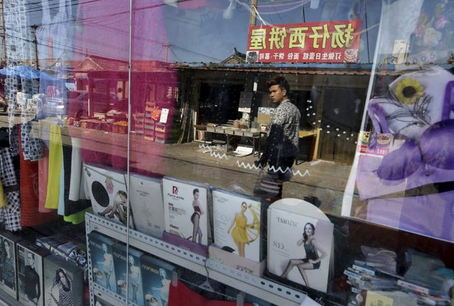 A man is reflected on the glass wall as he walks past a clothing shop inside a residential area for migrant workers on the outskirts of Beijing, China, October 13, 2015. (Photo by Jason Lee/Reuters)
