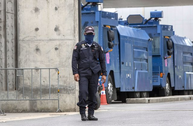 A police officer stands guard at the entrance to the Parliament building, lined with anti-riot vehicles ahead of a pro-democracy rally outside in Bangkok, Thailand, Thursday, September 24, 2020. Lawmakers in Thailand are expected to vote Thursday on six proposed amendments to the constitution, as protesters supporting pro-democratic charter reforms gathered outside the parliament building. (Photo by Gemunu Amarasinghe/AP Photo)