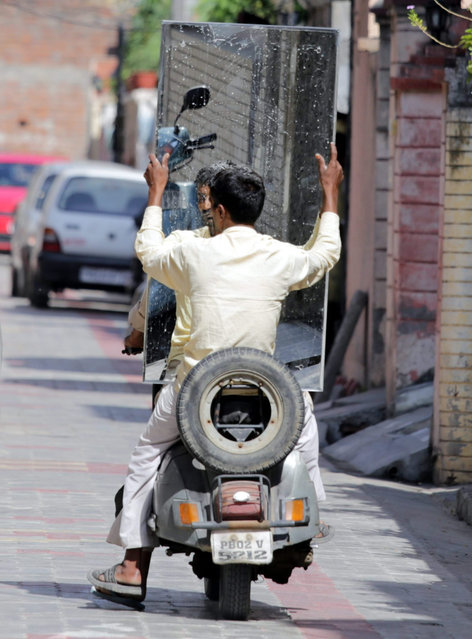 An Indian man sits holding a mirror on the rear seat of a scooter in a street in Amritsar, India, 21 October 2015. (Photo by Raminder Pal Singh/EPA)