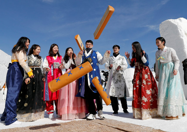 People dressed in traditional Korean clothes play a game as they celebrate Lunar New Year among ice sculptures in Pyeongchang, South Korea, February 16, 2018. (Photo by Eric Gaillard/Reuters)