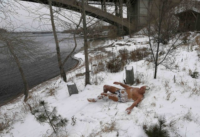 Ivan Abrosimov, 78, a member of a local winter swimmers' club, rolls around in snow before bathing in the Yenisei River in sub-zero temperatures in Russia's Siberian city of Krasnoyarsk, November 23, 2014. (Photo by Ilya Naymushin/Reuters)