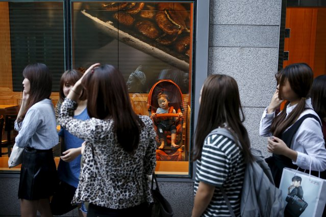 "Participants arrive to take part in TV program ""The Body Show"" at a gym as a baby in a stroller looks on in Seoul, September 19, 2015. (Photo by Kim Hong-Ji/Reuters)"