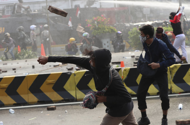 A protesters hurls a brick towards police trying to contain a rally in Jakarta, Indonesia, Thursday, October 8, 2020. (Photo by Achmad Ibrahim/AP Photo)