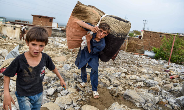A young villager retrieves belongings from the debris of houses after a flash flood affected the area at Sayrah-e-Hopiyan in Charikar, Parwan province, on August 26, 2020. The death toll from flash floods that swept through an Afghan city climbed to 100 on August 26, officials said, as rescue workers searched for survivors in the rubble of collapsed houses. (Photo by Wakil Kohsar/AFP Photo)