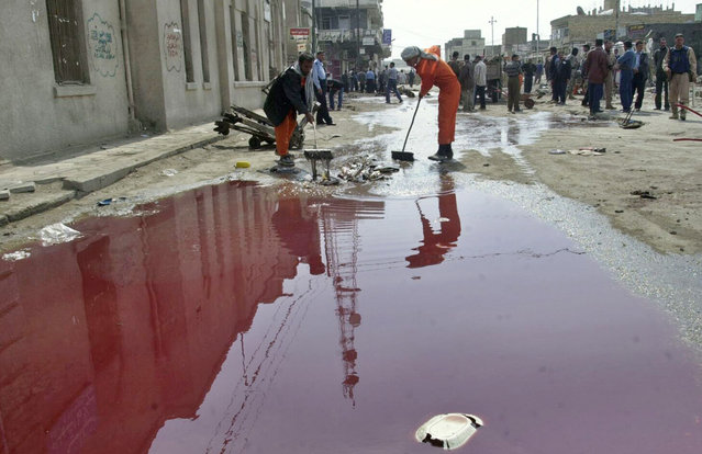 Iraqi workers clean debris near a large pool of blood at the scene of a suicide attack in the city of Hilla, on February 28, 2005. A suicide bomber detonated a car near police recruits and a crowded market, killing 115 people. (Photo by Ali Abu Shish/Reuters/The Atlantic)