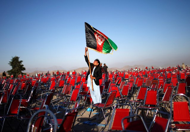 A supporter of Afghan presidential candidate Abdullah Abdullah holds an Afghan flag after an election campaign rally in the Paghman district of Kabul, in this June 9, 2014 file photo. (Photo by Ahmad Masood/Reuters)