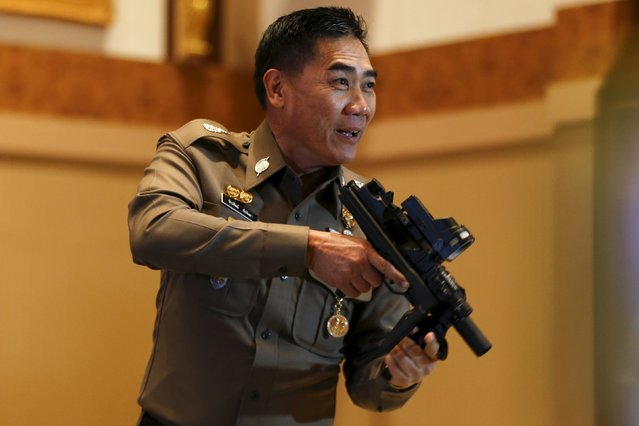 Thailand's national police chief Jakthip Chaijinda jokes with a confiscated weapon during a news conference at Royal Thai Police headquarters in Bangkok October 28, 2015. Thai police widened a major probe into a network of people charged with insulting the monarchy, which has seen three people charged for allegedly claimed false connections to the royal family and eight police officers demoted so far. (Photo by Jorge Silva/Reuters)