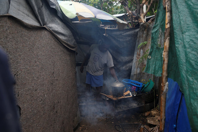 A man cooks a meal for his family at a camp for displaced people while Hurricane Matthew approaches Port-au-Prince, Haiti, October 3, 2016. (Photo by Carlos Garcia Rawlins/Reuters)