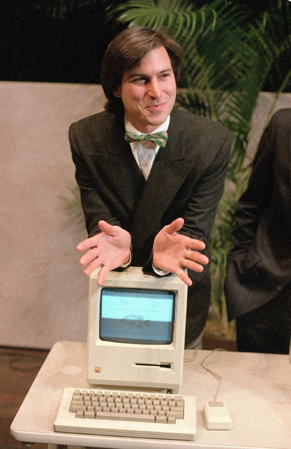 """Steven Jobs, chairman of the board of Apple Computer, leans on the new """"Macintosh"""" personal comptuer following a shareholder's meeting January 24, 1984 in Cupertino, Ca. The Macintosh, priced at $2,495, is challenging IBM in the personal computer market. (Photo by Paul Sakuma/AP Photo)"""