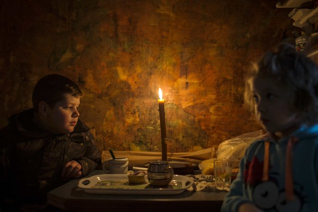Lazar and his sister Andjelka sit by a candle in their home in the eastern Serbian town of Majdanpek, December 4, 2014. Electricity workers in Serbia struggled through snow, ice and treacherous terrain on Thursday to restore electricity to an eastern town left shivering without power, heating or running water for a fourth day. (Photo by Marko Djurica/Reuters)