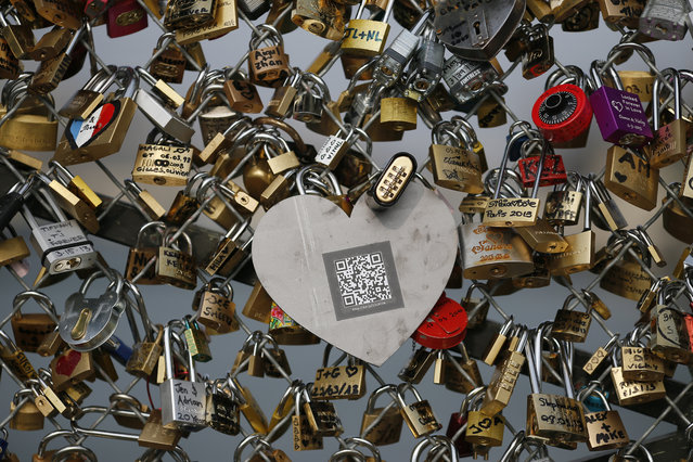 """A picture taken on April 4, 2013 at the """"Pont des Arts"""" in Paris shows one of the black heart-shaped padlocks symbolizing abused women which the French feminist movement """"Ni Putes, Ni Soumises"""" (Neither Whores Nor Submissive – NPNS) founded in 2002 asked individuals to place on the bridge to mark its tenth anniversary. (Photo by Kenzo Tribouillard/AFP Photo)"""