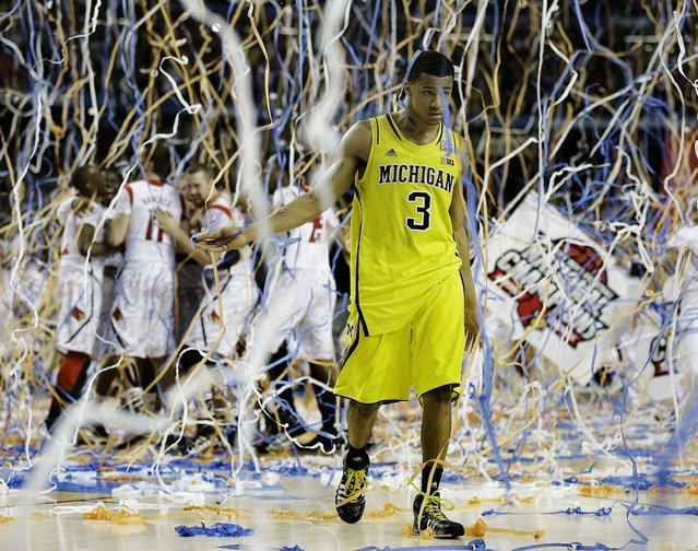 Michigan guard Trey Burke walks off the court as Louisville players celebrate their championship, on April 8, 2013. (Photo by Charlie Neibergall/Associated Press)