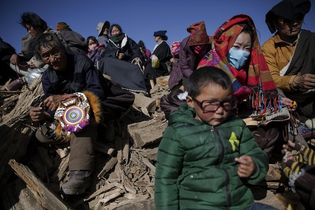 Ethic Tibetans wait for hot tea and food to be distributed on a hill where people gather to listen Buddhist monks' teaching above Larung Wuming Buddhist Institute in remote Sertar county, Garze Tibetan Autonomous Prefecture, Sichuan province, China October 31, 2015. (Photo by Damir Sagolj/Reuters)