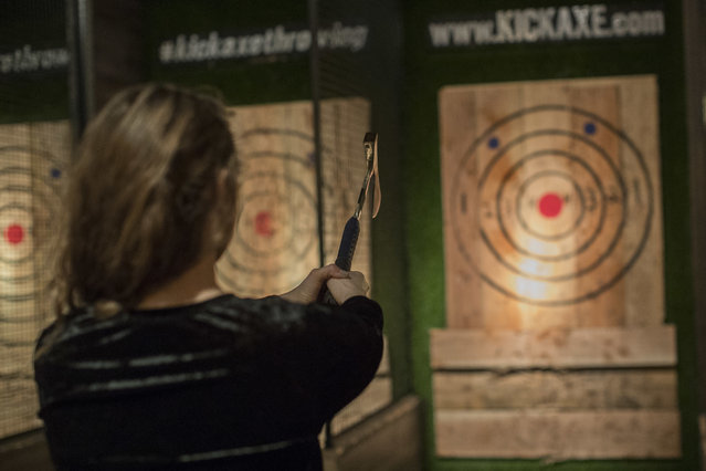 "In this Saturday, March 3, 2018, photo, a contestant prepares to throw a hatchet at a wooden bullseye at the Kick Axe Throwing venue in the Brooklyn borough of New York. Kick Axe Throwing is the first bar in New York City to pick up on a nationwide trend of ax throwing, a growing sport that some enthusiasts hope will take off the way bowling did in the last century. ""People are like, ""Sharp objects and beer? What a great idea that is"". But truthfully, after you have a couple drinks you start to actually throw a little bit better"", said Alexander Stine, an ""axepert"" at Kick Axe. He honed his own skills growing up in Colorado throwing knives at carnivals and now trains newcomers on proper technique. ""It's about believing in your ability to do something you didn't think you could do before"". Scoring is similar to darts. Players aim at a wooden board painted with a bull's-eye and rings corresponding to different point values. Playing to the sport's origins at Canadian logging competitions, Kick Axe's decor is reminiscent of a ski lodge, complete with flannel chairs and calfskin carpeting. The perimeter of the venue is lined with cages for throwing. There's a bar serving wine and beer, but no hard liquor. Guests can take a break from throwing axes to play board games like ""Candy Land"" at tables in the center of the room. While Kick Axe mainly caters to casual players, there are locations across the country where enthusiasts play the sport competitively. There was no alcohol in sight during recent tournament play at Chicago's Bad Axe Throwing, a Canada-based chain of 18 venues. Bad Axe's CEO, Mario Zelaya, founded the World Axe Throwing League a year ago. He said it now has 2,500 members worldwide who compete at his own locations and other independent venues. ""It's bowling 2.0"", said Zelaya. ""What bowling maybe used to be in the 80's and 90's and this is what ax throwing is right now. It's fun. It's new. It's addictive. It's active entertainment"". The World Axe Throwing League held its first world championship tournament in December. Competitors played in their home courts and the games were broadcast remotely on Facebook Live. The winner took home a $3,500 prize. Zelaya says his ultimate goal is to make ax throwing an Olympic sport. (Photo by Mary Altaffer/AP Photo)"