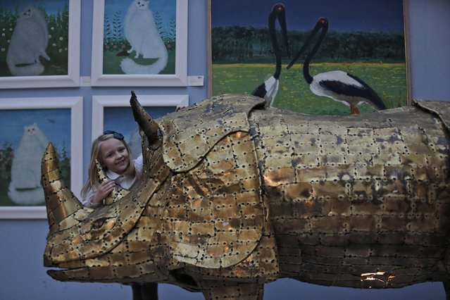 """A girl touches a bronze sculpture depicting a rhinockeros as she poses for the photographers during a press preview of a themed auction that features the animal as artistic inspiration, entitled the """"Creatures Great and Small"""", in London, Monday, December 15, 2014. (Photo by Lefteris Pitarakis/AP Photo)"""