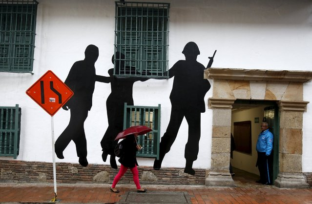 Citizens walk in front of a mural representing victims and missing people near the rebuilt Justice Palace in Bogota Colombia November 6, 2015. Colombian President Juan Manuel Santos on Friday apologized for military actions during a 1985 assault on Bogota's Palace of Justice by M-19 rebels, in which over 100 people died including nearly half of the country's Supreme Court justices. (Photo by John Vizcaino/Reuters)