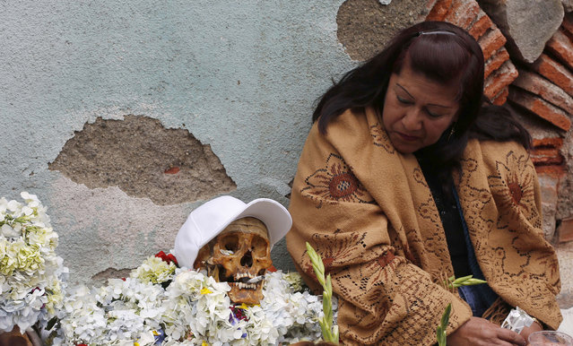 """A woman looks at her decorated human skull or """"natitas"""" as she waits to be greeted by the priest inside the Cementerio General chapel, during the Natitas Festival celebrations, in La Paz, Bolivia, Sunday, November 8, 2015. Although some natitas have been handed down through generations, many are from unnamed, abandoned graves that are cared for and decorated by faithful who use them as amulets believing they serve as protection. The tradition marks the end of the Catholic All Saints holiday, but is not recognized by the Catholic church. (Photo by Juan Karita/AP Photo)"""