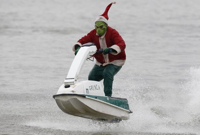 A jet ski rider, dressed as the Grinch, takes part in the 29th annual Christmas Eve water performance on the Potomac River in Alexandria, Virginia, December 24, 2014. (Photo by Larry Downing/Reuters)