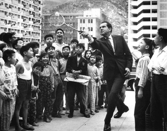 Children in a Hong Kong refugee resettlement area watch as former Vice President Richard Nixon shows them his badminton service. Nixon visited Hong Kong, April 4, 1964, during his tour of countries in the Far East. (Photo by AP Photo)