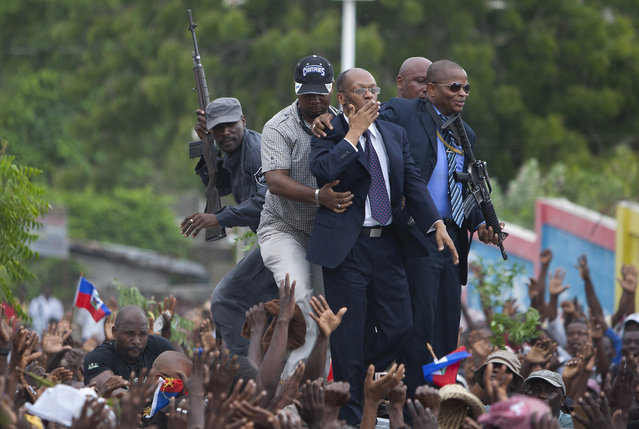 Flanked by bodyguards, former Haitian President Jean-Bertrand Aristide, center, greets supporters as leaves a courthouse in Port-au-Prince on May 8, 2013. Aristide had testified before a judge investigating the slaying of one of the country's most prominent journalists. (Photo by Dieu Nalio Chery/AP Photo)