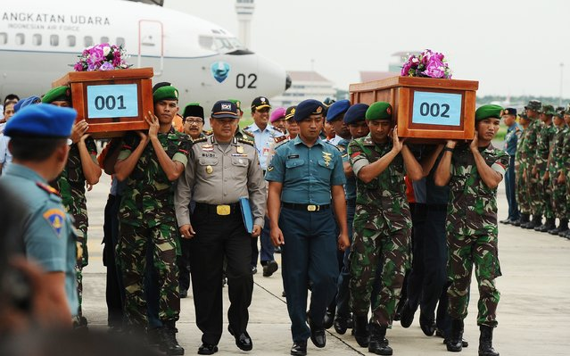 Indonesian soldiers carry coffins containing victims of the AirAsia flight QZ8501 crash at the Indonesian Air Force Military Base Operation Airport on December 31, 2014 in Surabaya, Indonesia. A massive recovery operation has begun following confirmation from Indonesian officials that remains and debris found in waters off Borneo are from the missing AirAsia plane.  (Photo by Robertus Pudyanto/Getty Images)