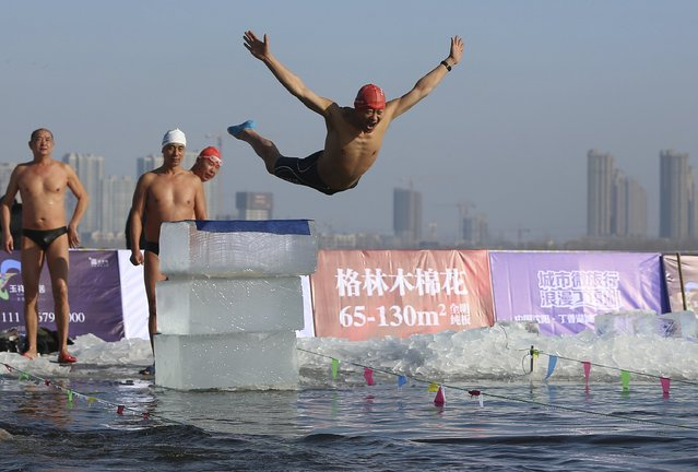 A man jumps into cold water during a contest in Shenyang, Liaoning province December 30, 2014. The winter swimming competition was held in Shenyang this Tuesday where 260 members from 40 teams participated, according to local media. (Photo by Reuters/Stringer)