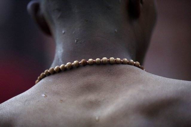 A devotee wearing prayer beads returns after taking a holy bath at the Saali River on the first day of the Swasthani Brata Katha festival at Sankhu in Kathmandu January 5, 2015. (Photo by Navesh Chitrakar/Reuters)