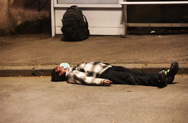 A man wearing a protective mask is on the ground unconscious near a bus stop before being helped by medical personnel as the spread of the coronavirus persists on March 22, 2020 in Rome, Italy. Italy continues its nationwide lockdown with a reported 793 deaths on Saturday but a drop to 651 so far on Sunday due to COVID-19. (Photo by Marco Di Lauro/Getty Images)