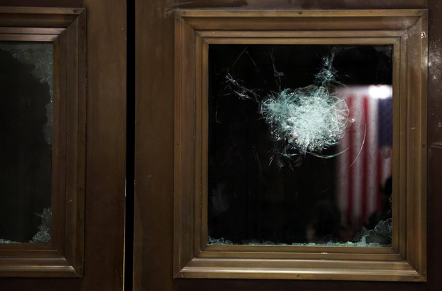 A broken window is seen during a joint session of Congress after they reconvened to certify the Electoral College votes of the 2020 presidential election in the House chamber in Washington, U.S. January 7, 2021. The House and Senate certified the Democrat's electoral college win early Thursday after a violent throng of pro-Trump rioters spent hours Wednesday running rampant through the Capitol. A woman was fatally shot, windows were bashed and the mob forced shaken lawmakers and aides to flee the building, shielded by Capitol Police. (Photo by Jonathan Ernst/Reuters)
