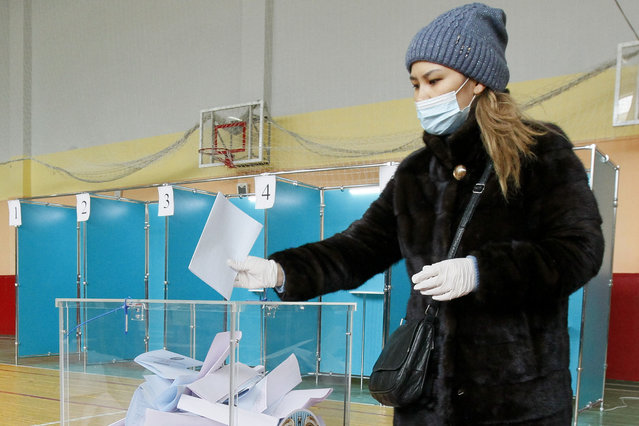 A woman wearing a face mask and gloves to protect herself against coronavirus, casts her ballot at a polling station during a parliamentary elections in Nur-Sultan, the capital city of Kazakhstan, Sunday, January 10, 2021. (Photo by AP Photo/Stringer)