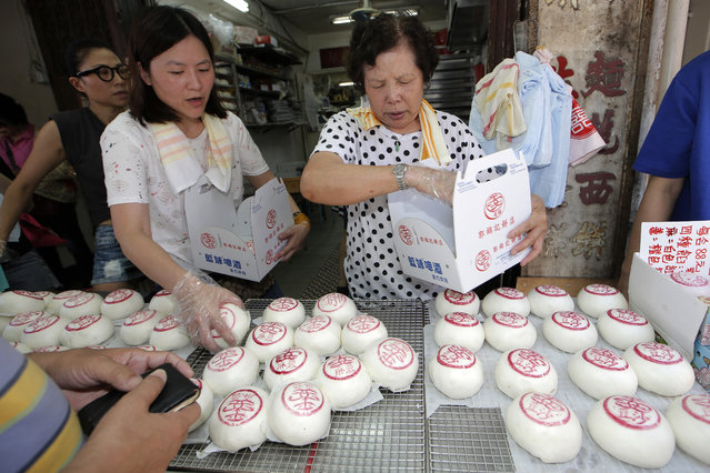 """Shopkeepers sell the buns with the sign featuring the Chinese character """"Peace"""" on the outlying Cheung Chau island in Hong Kong to celebrate the Bun Festival Tuesday, May 22, 2018. (Photo by Kin Cheung/AP Photo)"""