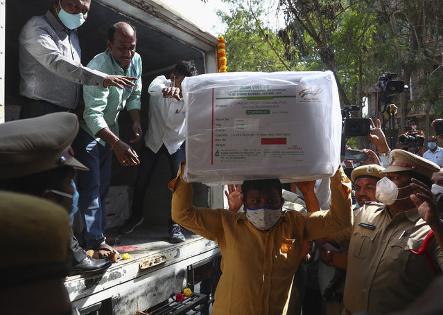 In this January 12, 2021, file photo, health workers shift a box containing COVID-19 vaccine from a vehicle to a cold storage at Commissionerate of Health and Family Welfare in Hyderabad, India. The global death toll from COVID-19 has topped 2 million. (Photo by Mahesh Kumar A./AP Photo/File)